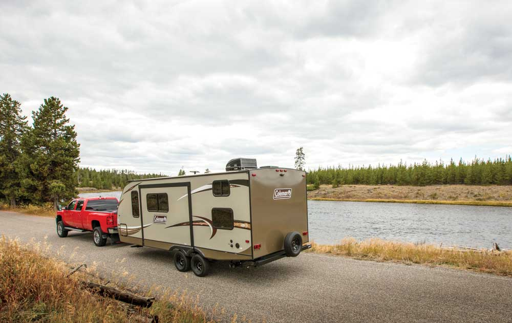 Truck towing travel trailer on a forest road next to a river