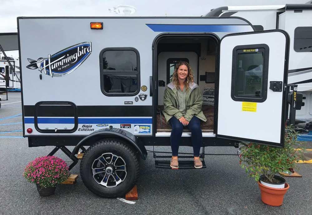 A RV show attendee sits inside a teardrop trailer