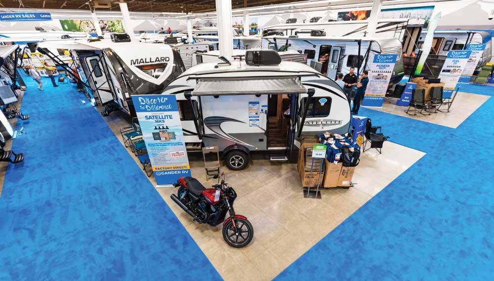 Several RVs on display at an RV show