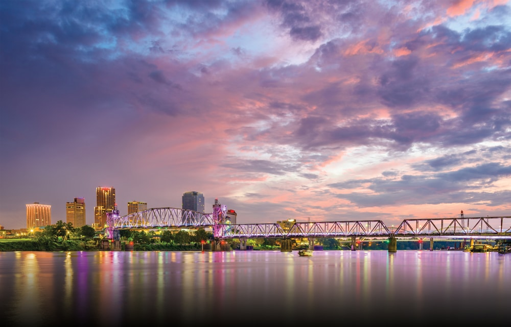 A pedestrian bridge over the Arkansas River with city lights and sunset sky