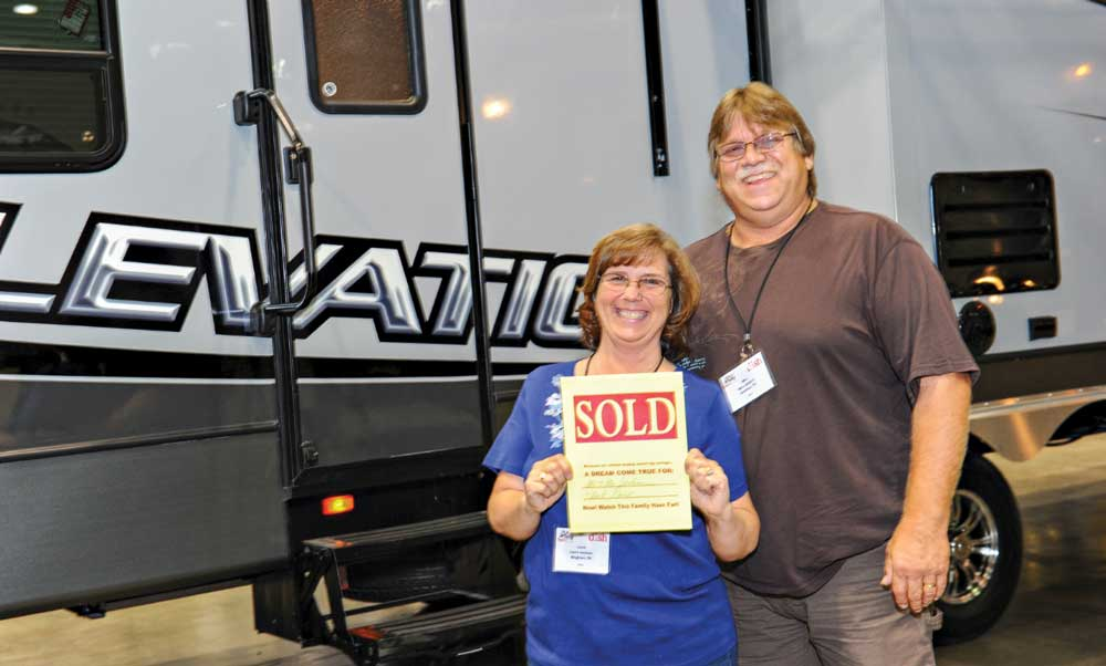 A couple shows of the sold sign after closing a deal on their new RV