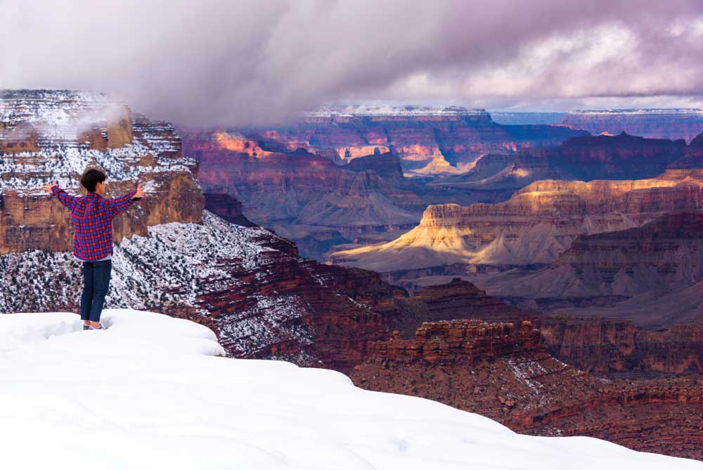 A visitor revels in a winter view of Grand Canyon