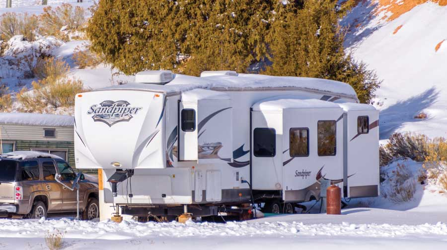 A Fifth-Wheel trailer parked in a snow-covered campsite