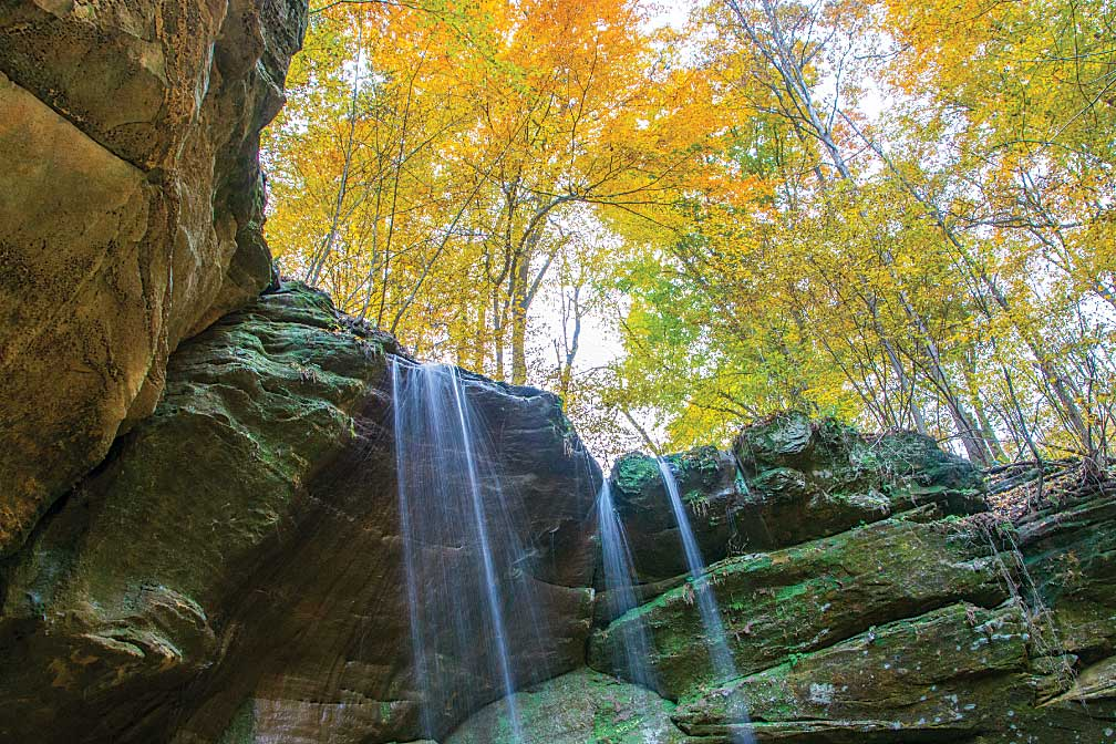 Big Lyons Falls in Mohican State Park is shown with fall colors in the surrounding forest