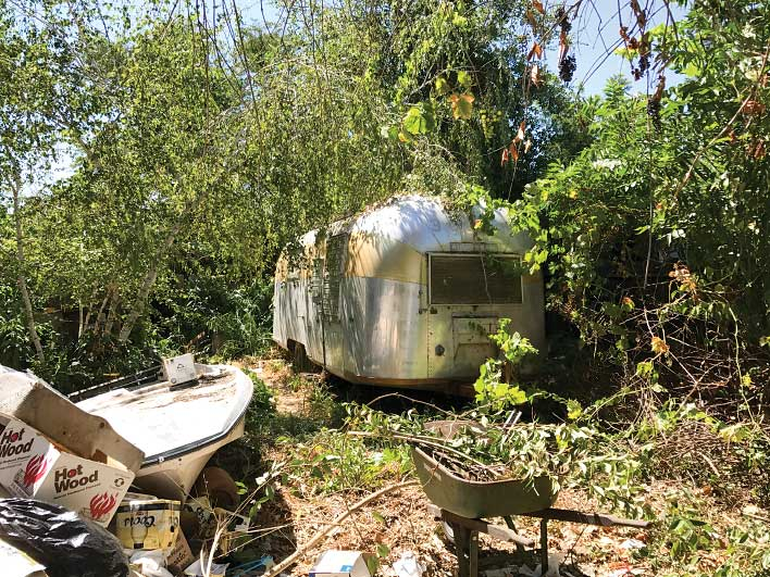The 1961 airstream before restoration, buried behind bushes and trash