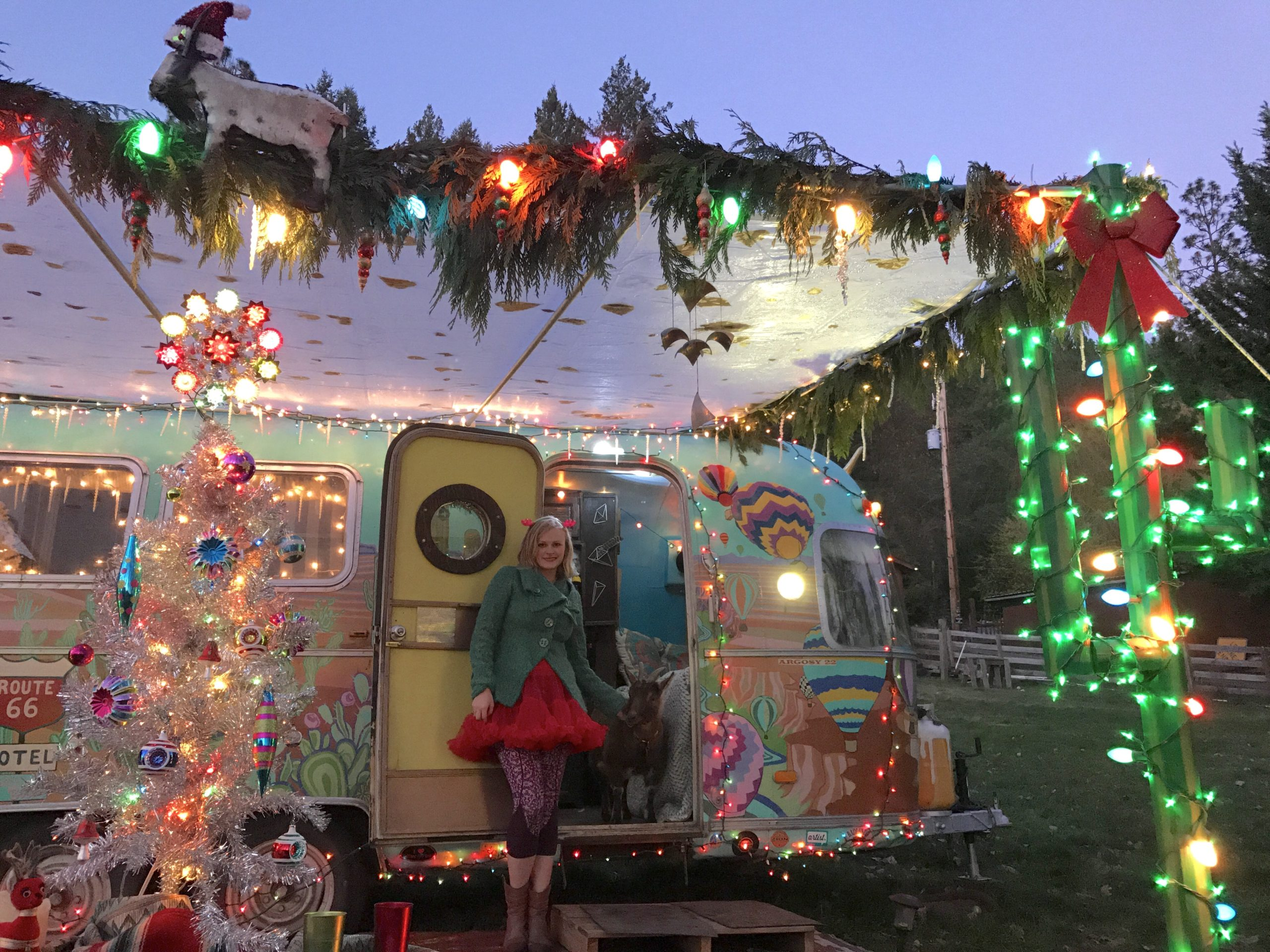 Woman with blonde hair dressed in Christmas colored skirt and coat posing in front of decorated travel trailer