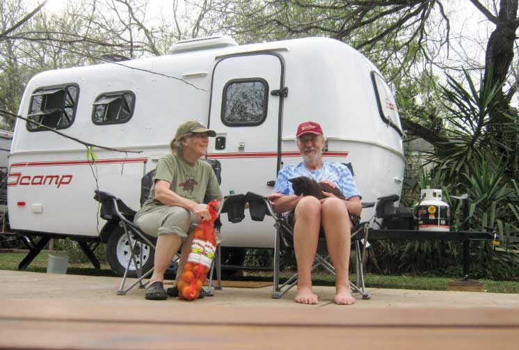 The author and his wife, Janet, with their cat, Zeke relax outside their travel trailer