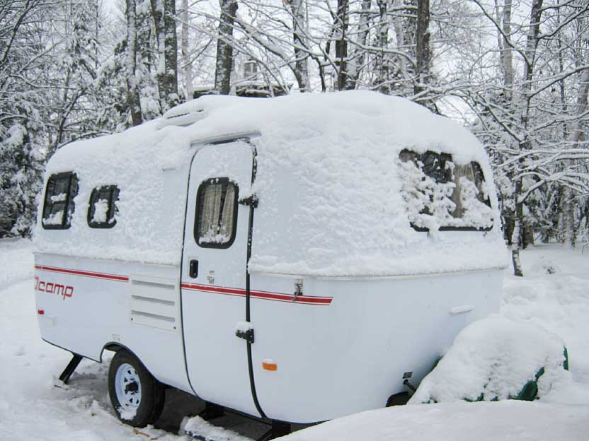 A Scamp travel trailer covered in snow