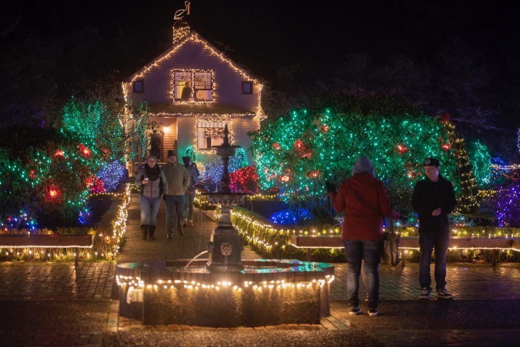 People walking along street near houses covered in holiday lights, dressed warmly