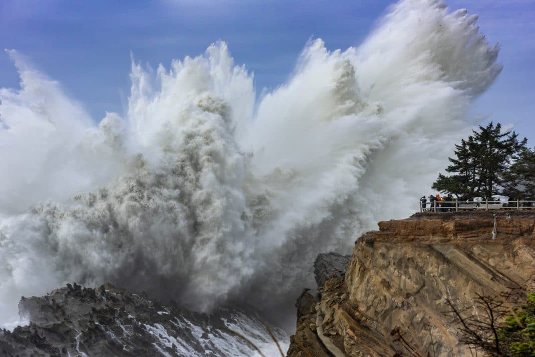 Massive ocean swell crashing on large rocky cliff during the day in Oregon