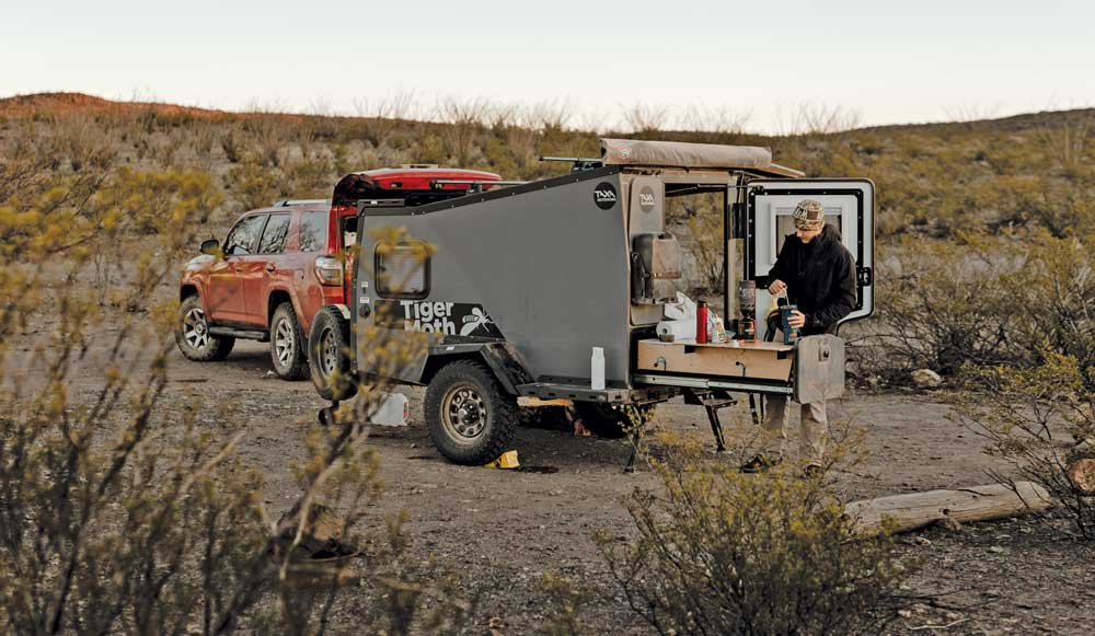 A camper prepares a beverage in the outdoor kitchen of the Taxa Outdoors Tigermoth