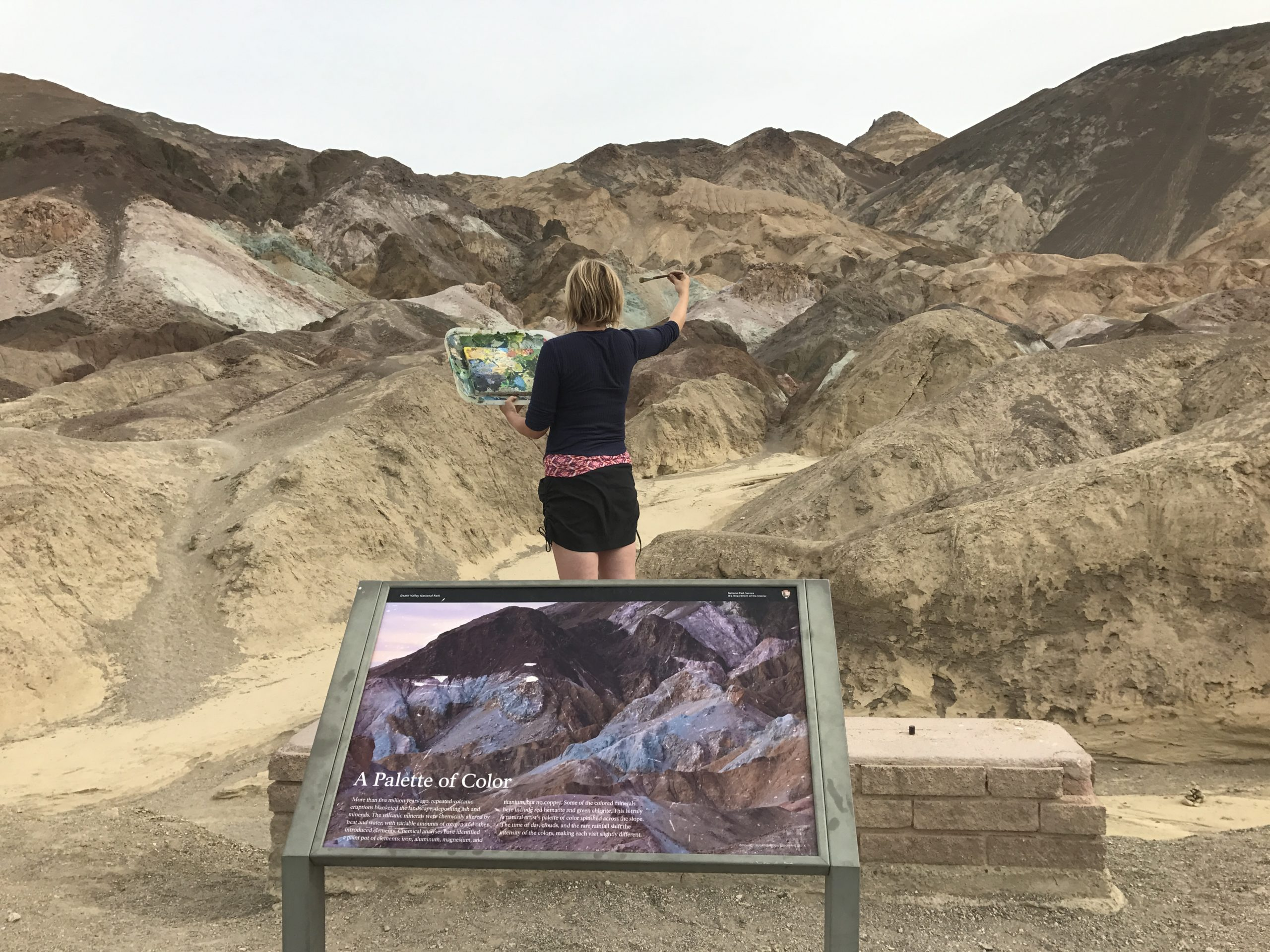 Woman's back looking towards hills holding artists pallet in Death Valley
