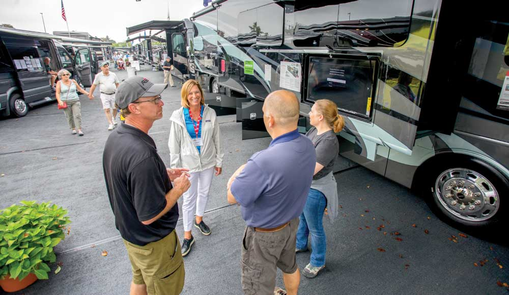 RV shoppers converse with RVs in the background at an RV show