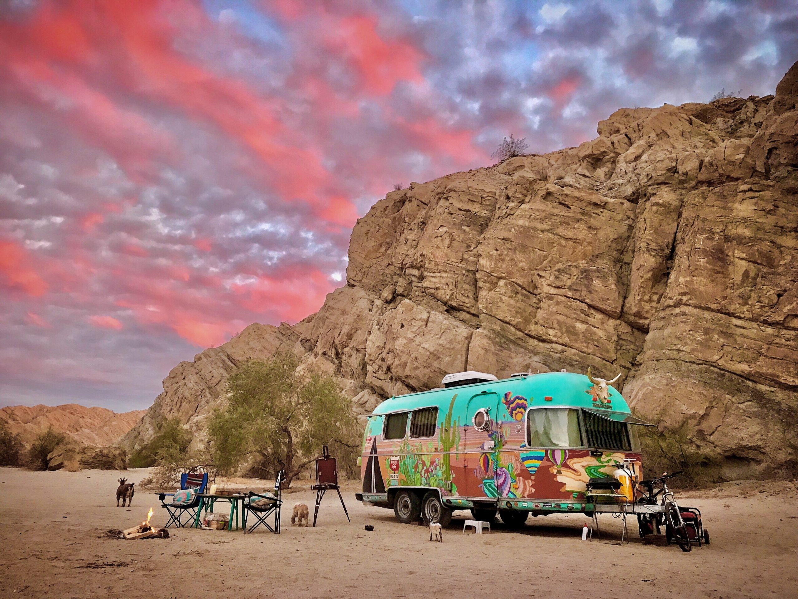 Colorful Airstream trailer parked against Joshua Tree mountain with beautiful pink and purple clouss
