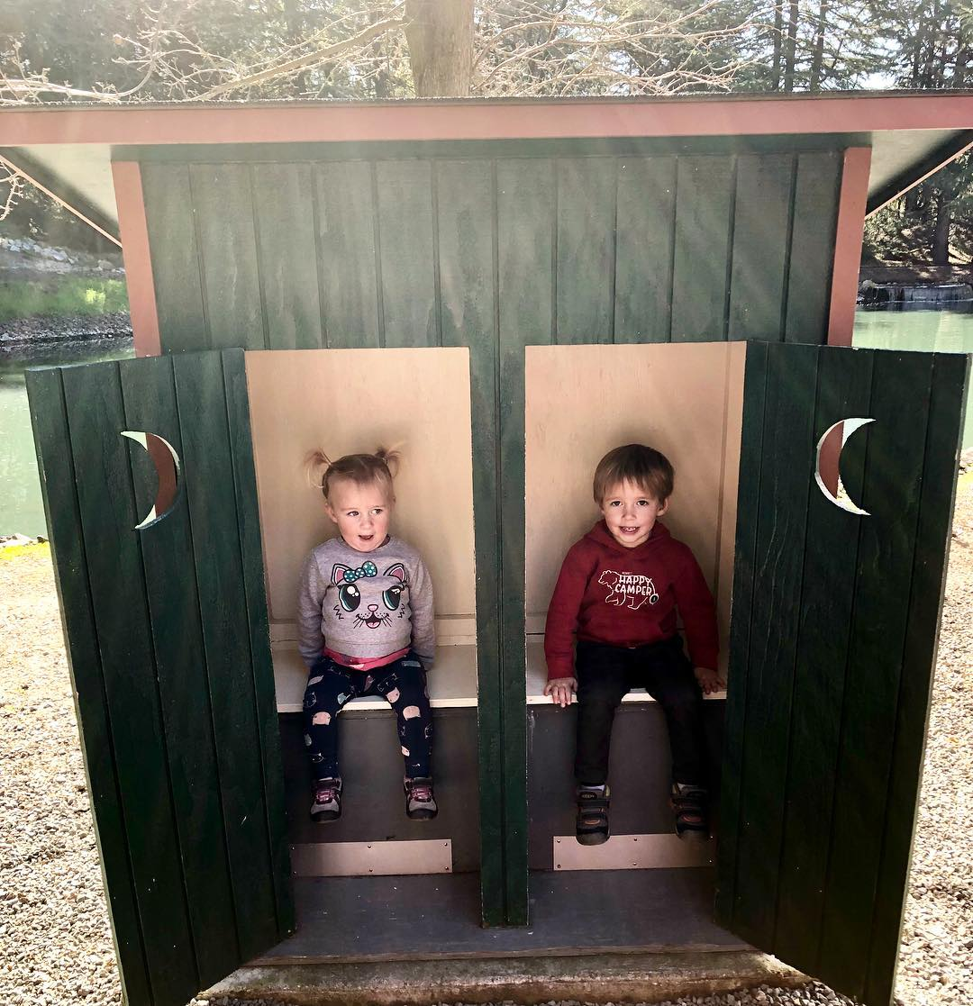 Two toddlers sitting and smiling in outdoor bathroom