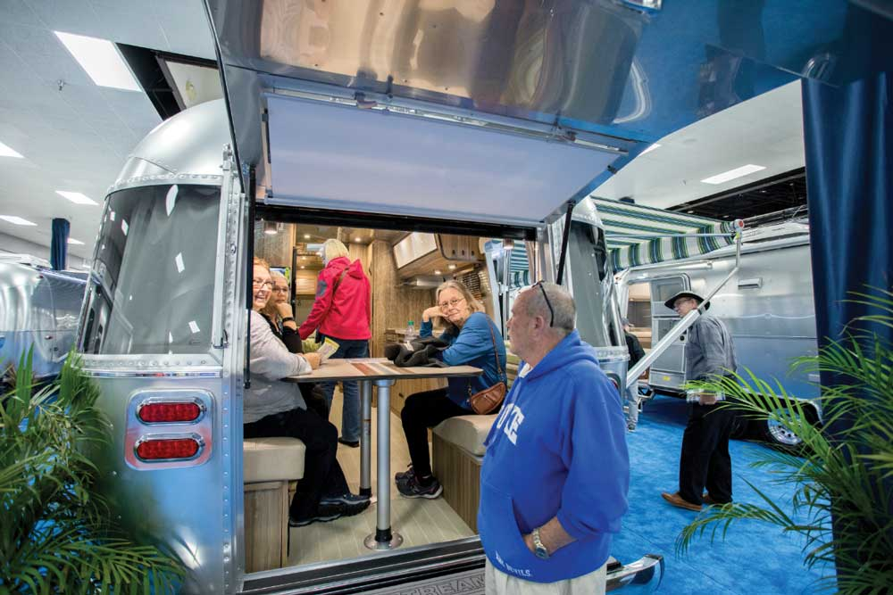A family sizes up an RV dinette at an RV show