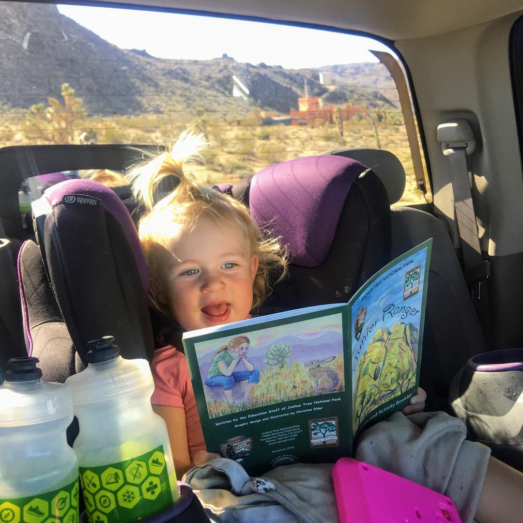 Toddler reading child's book in back of car