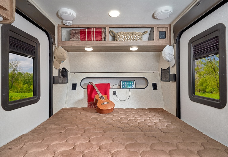 View toward the front interior of the Jayco Hummingbird 10RK showing the bed with a guitar on it.