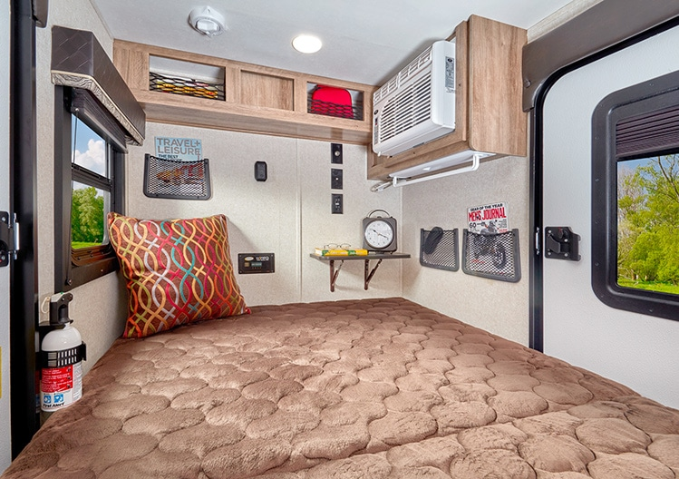 Inside view of the Jayco Hummingbird 10RK looking toward the rear with overhead storage and air-conditioning unit.