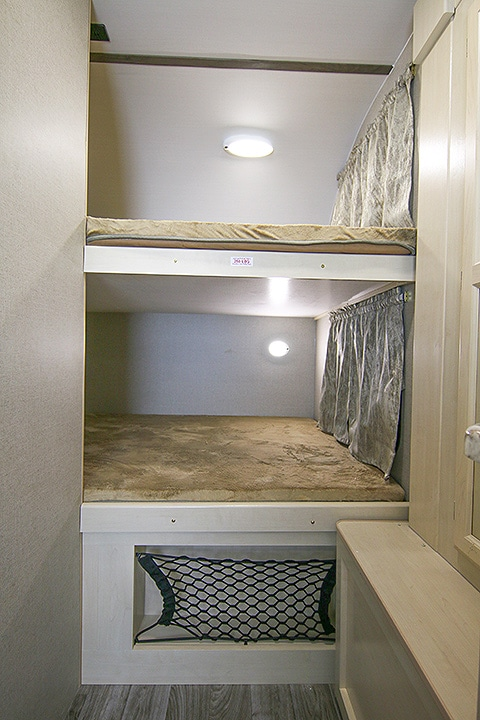 Bunk beds in the rear of the trailer with lighting inside and storage below.