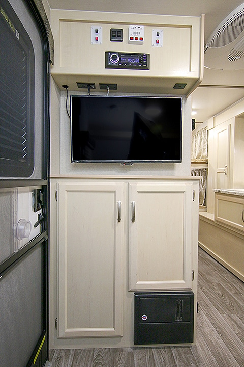 A flat-screen TV and cupboards in cream color.