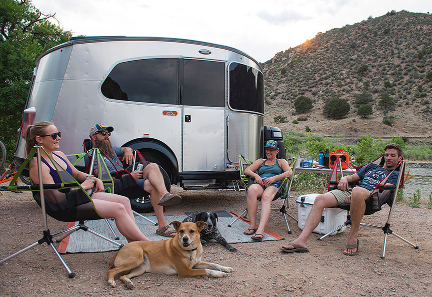 Four people in camp chairs and a dog in front of the Basecamp trailer.
