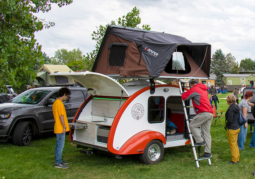 Classic Bean trailer with a rooftop tent accessed by man on ladder.