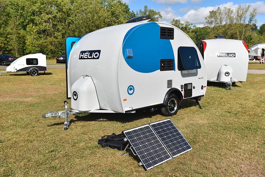 Three small camping trailers on grassy field with solar panel in front.