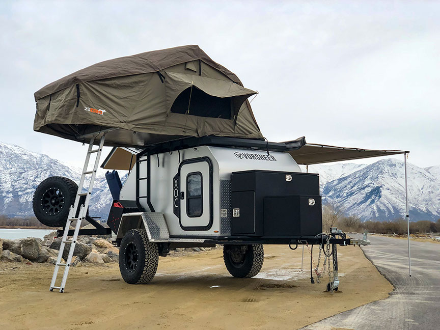 Vorsheer XOC trailer parked with rooftop tent extended and snowy mountains in background.