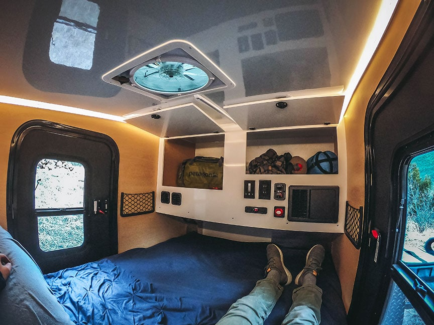 Person reclining on bed of trailer with cupboards straight ahead.