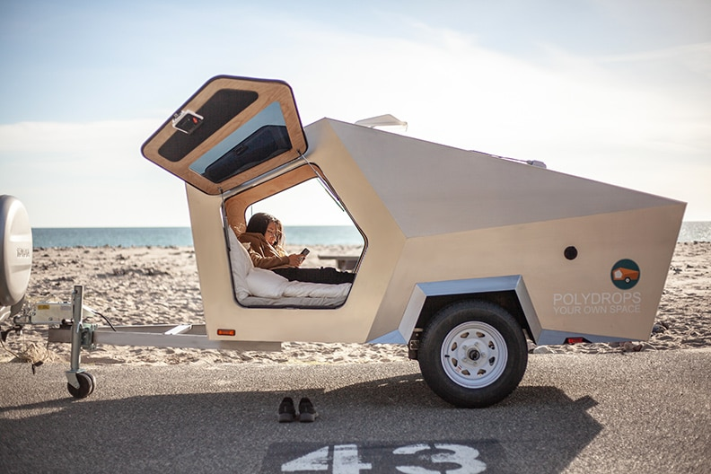 Polygon trailer with doors open and a woman inside at the beach.