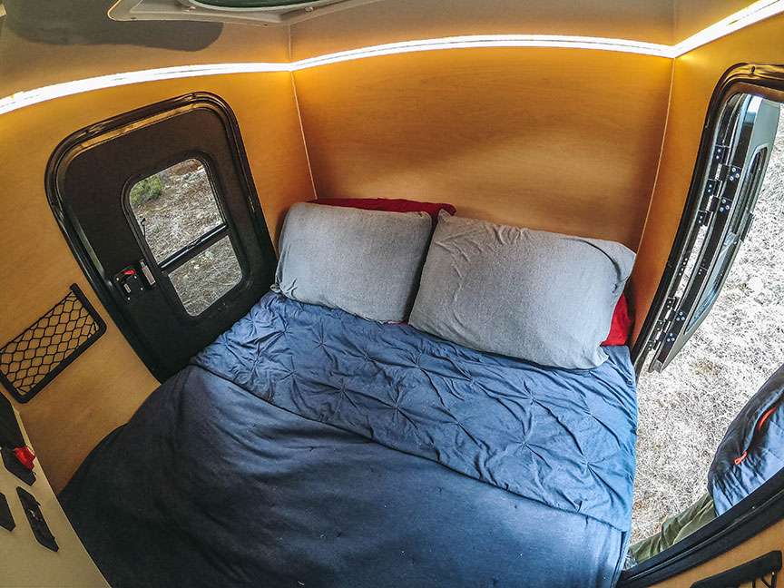 Back of trailer with two pillows on bed and two entry doors.