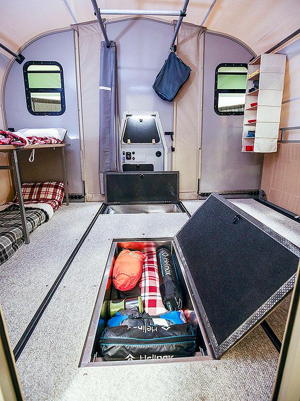 Inside view of trailer with storage panel in floor open.
