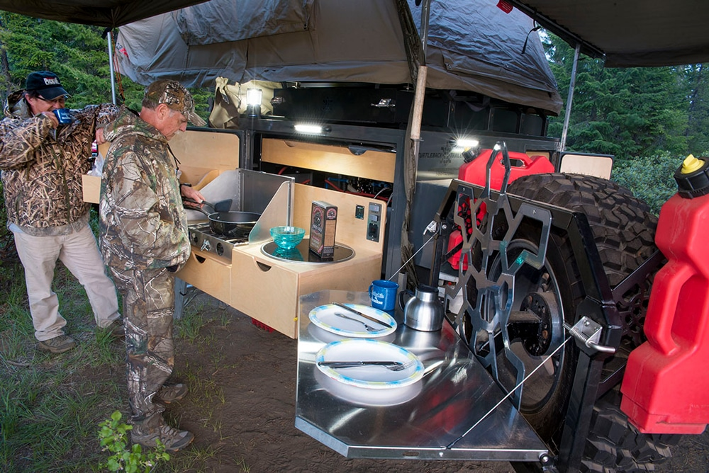 The rear door of the Expedition swings open to reveal the built-in galley. The stainless-steel table folds up flat to store against the spare tire.