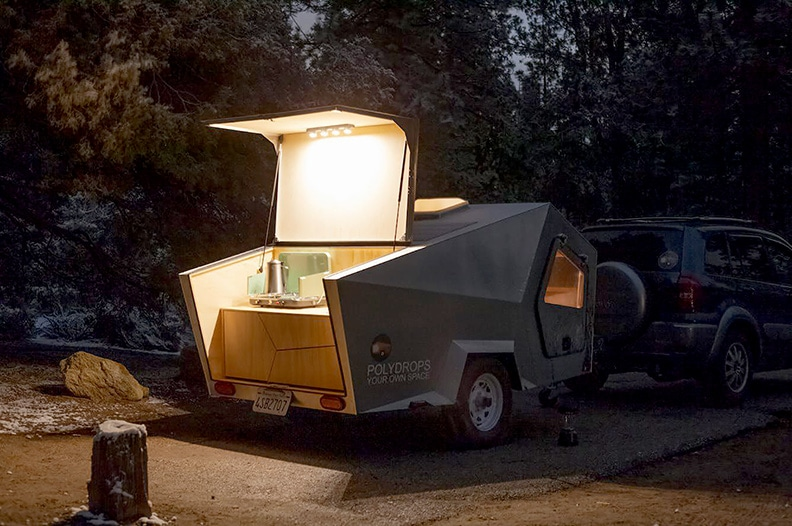 Rear hatch opens to reveal the kitchen , shown at night with lights.