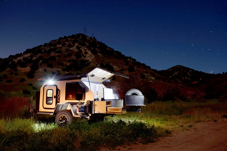 Night scene of trailer with lights on and starry sky above.