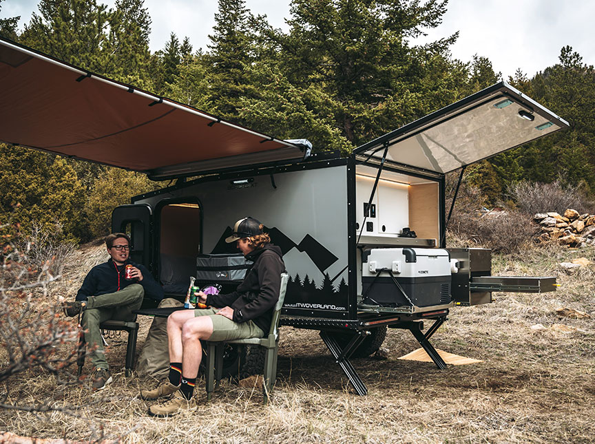 Two people in camp chairs in front of trailer with awning extended.