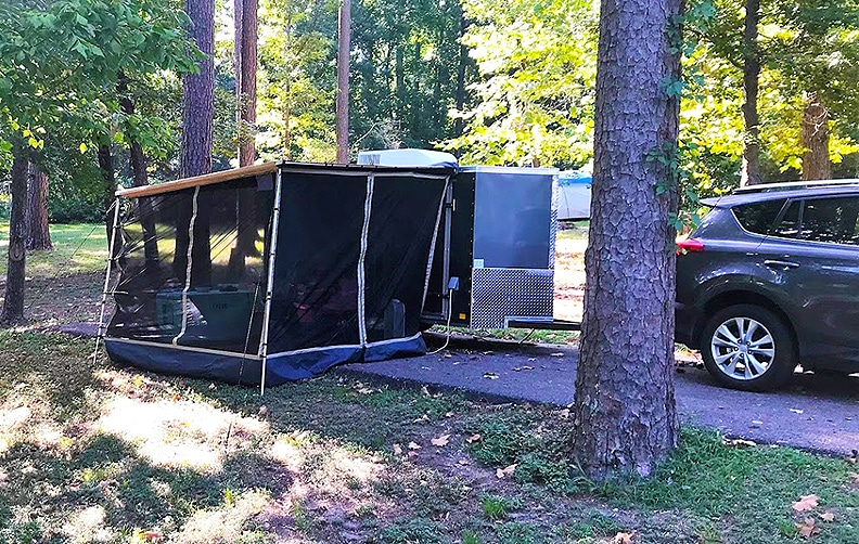 Cargo camp in campsite with screened room on awning and SUV tow vehicle.