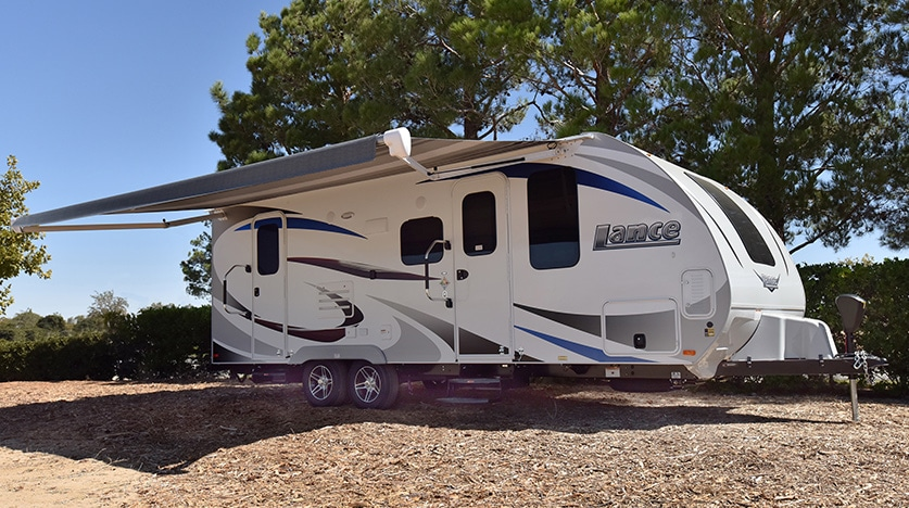 Exterior of white Lance trailer with awning extended.