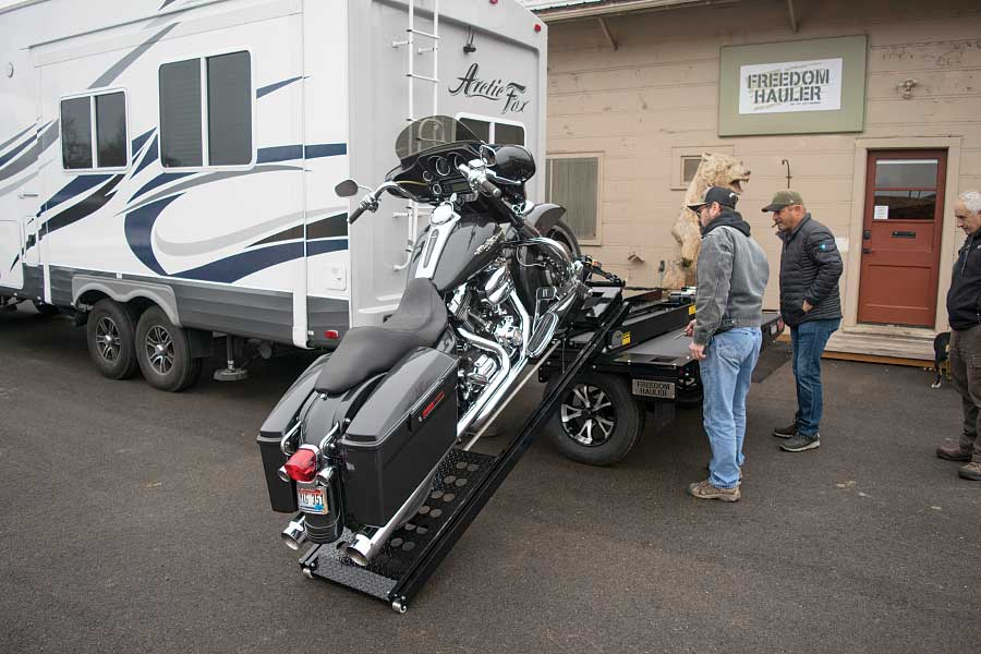 Two men load a motorcycle onto the freedom Hauler behind a fifth-wheel trailer