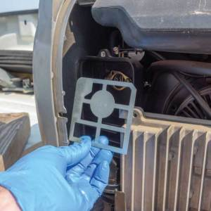 Clean any dust around the edges of the air-filter compartment and wipe down the metal divider that holds the filter. Put the filter and its cover back in place and screw the generator's side panel back on.