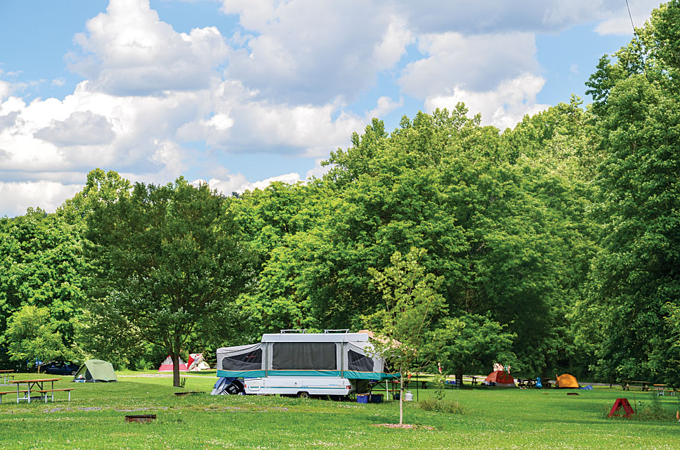 Popping up in a sea of green, a folding camper at Robert H. Treman State Park is surrounded by picnic tables, restrooms with showers, and hiking trails that lead to numerous waterfalls.