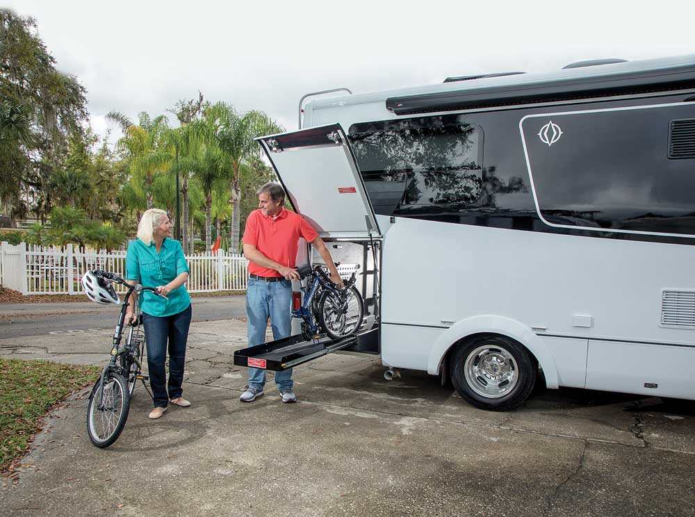 A couple unloads bicycles from the Leisure Travel Vans Wonder W24RTB