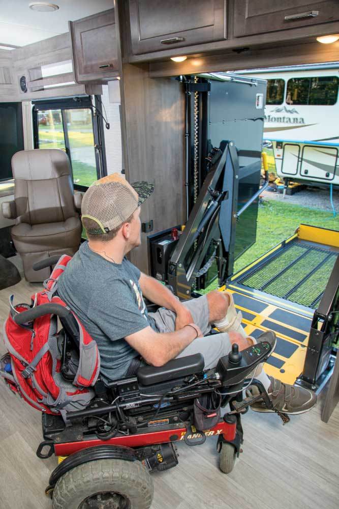 A man in a wheel-chair prepars to exit the Winnebago Adventurer 30T AE using the 800-pound-capacity BraunAbility power lift that extends outward.