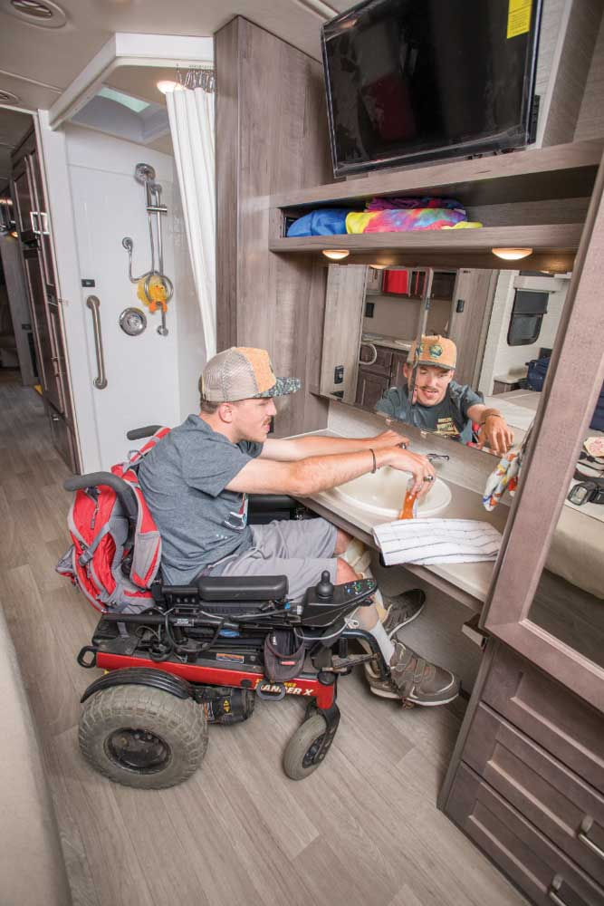 A man in a wheel-chair makes use of the second vanity with roll-under 27-inch vertical clearance in the Winnebago Adventurer 30T AE.