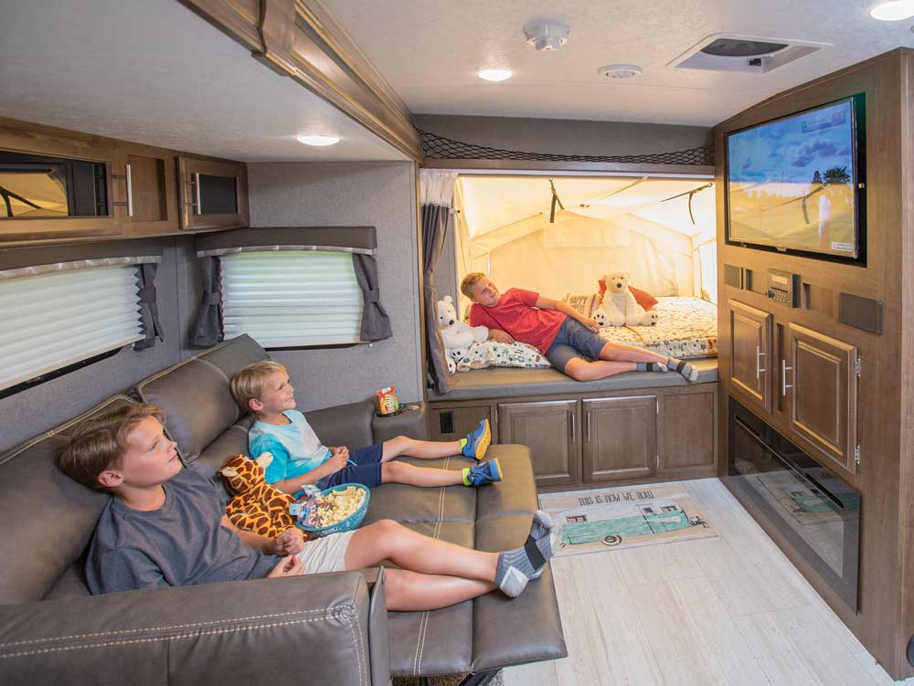 A family enjoys TV and snacks in the living area of the 2020 ROCKWOOD ROO 235S hybrid travel trailer