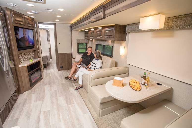 A couple lounges on the sofa of a Entegra Coach Accolade 37K