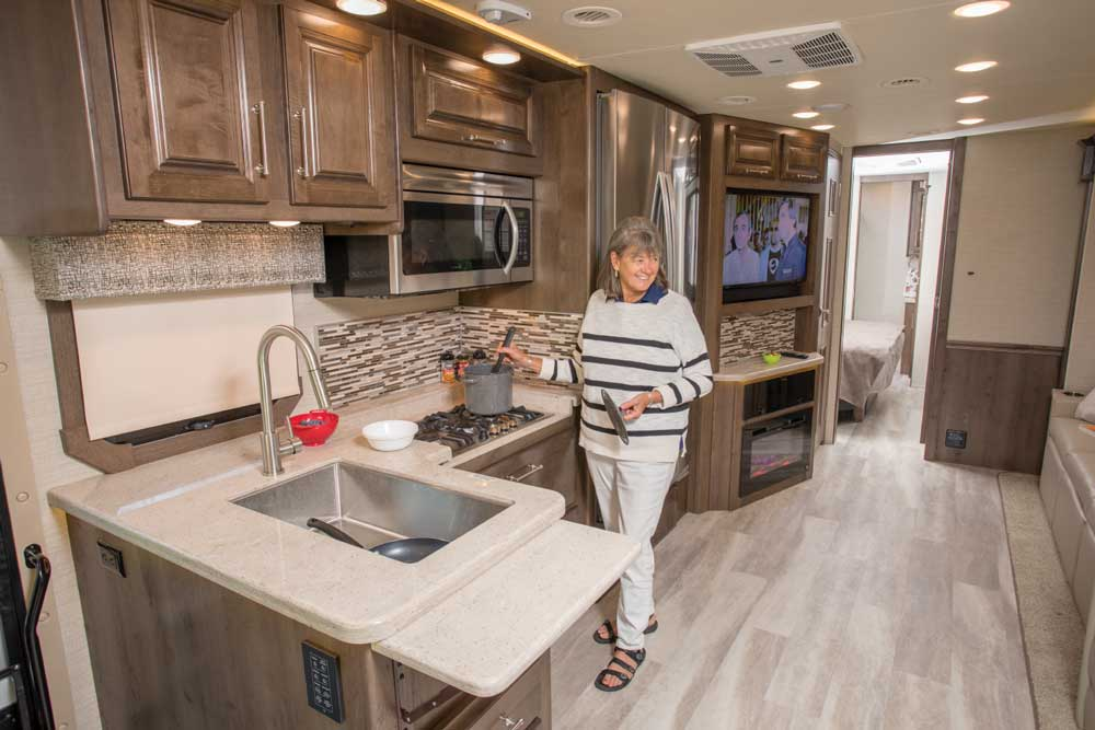 A woman stands in the galley of a Entegra Coach Accolade 37K