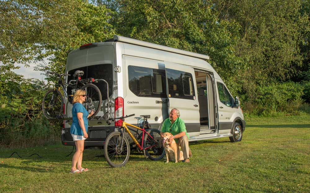 A couple and their dog chat outside the 2020 Coachmen Beyond 22C