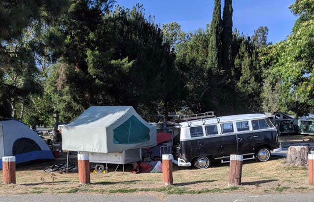 A black-and-white 1966 VW bus and 1969 Heilite pop-up camper under the shade of trees.